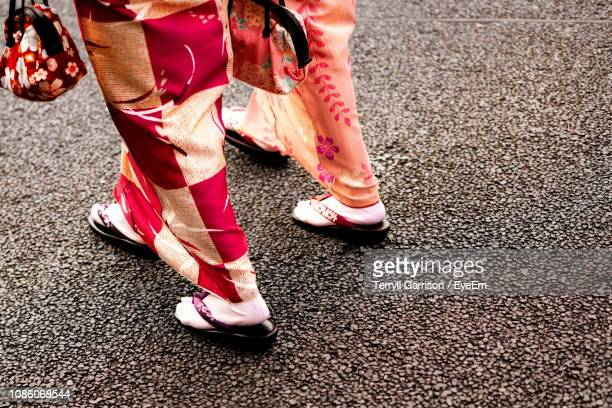 low section of women in traditional clothing walking on road - 人の足 ストックフォトと画像