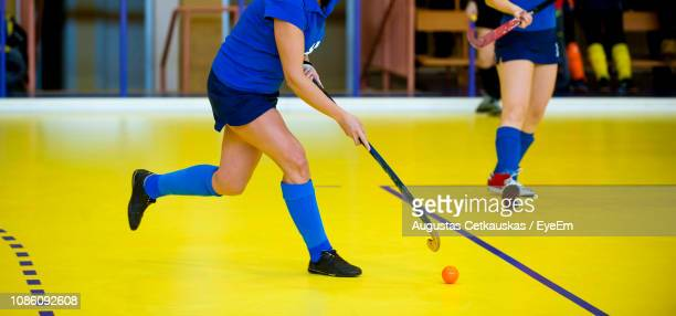 low section of women playing hockey - hockey stick stock pictures, royalty-free photos & images