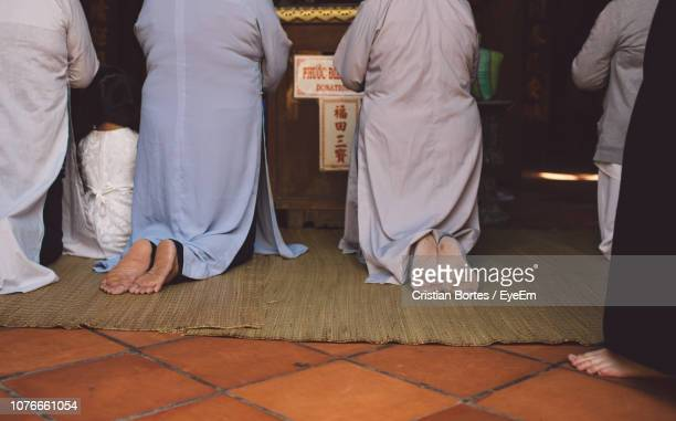 Low Section Of Women Praying In Shrine