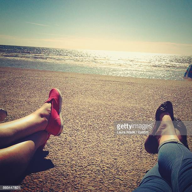 Low Section Of Women Relaxing On Beach