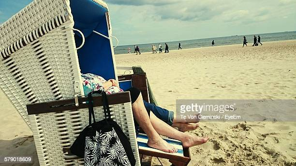Low Section Of Women Resting In Hooded Beach Chair