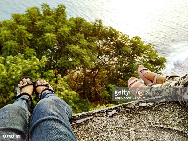 low section of women sitting against sea - tari stock pictures, royalty-free photos & images