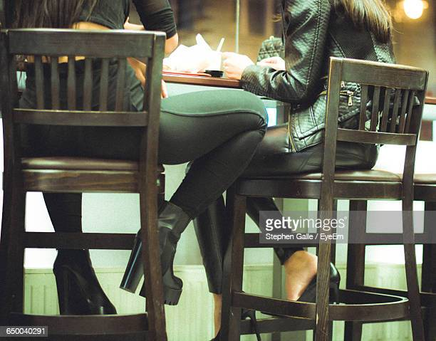 Low Section Of Women Sitting In Restaurant