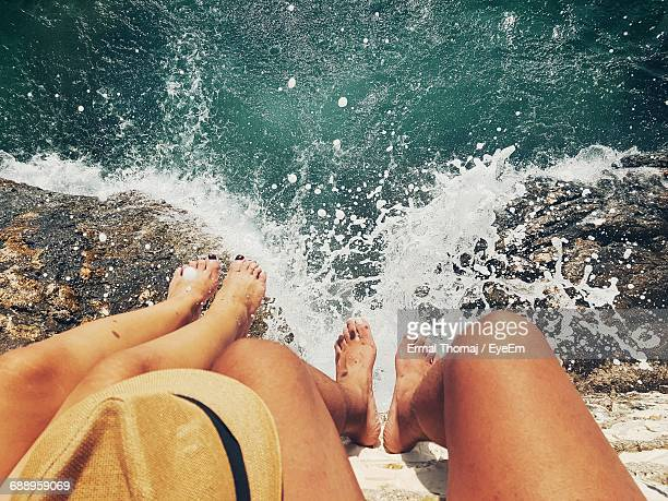 low section of women sitting on retaining wall by sea - tirana stock pictures, royalty-free photos & images