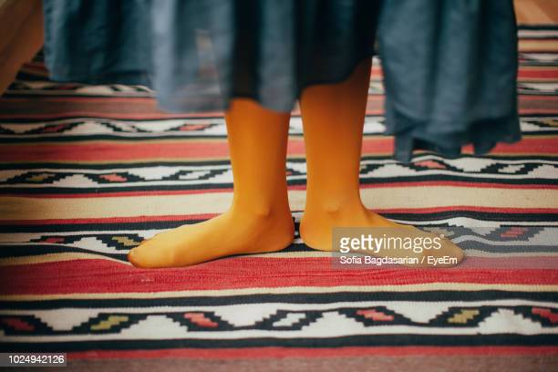 low section of women standing on carpet - stockings no shoes stock photos and pictures
