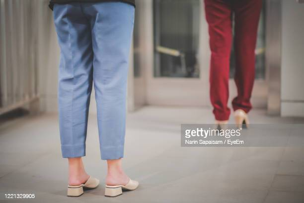 low section of women standing on floor - frau gespreizte beine stock-fotos und bilder