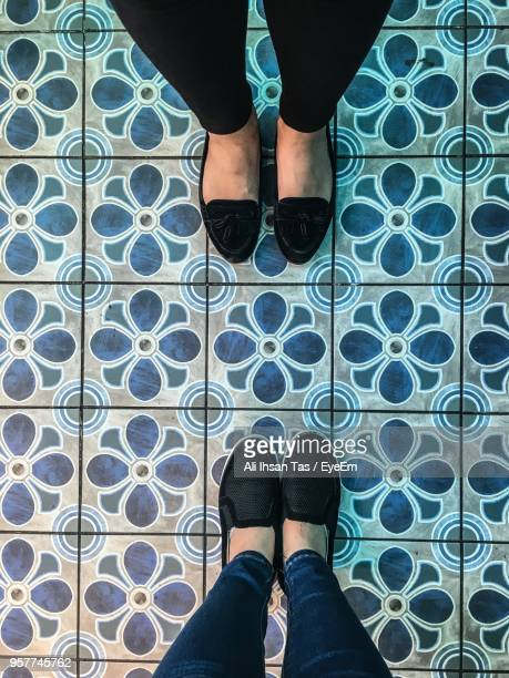 low section of women standing on tiled floor - sezione inferiore foto e immagini stock
