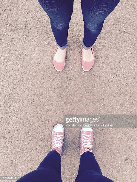 Low Section Of Women Standing With Pink Footwear