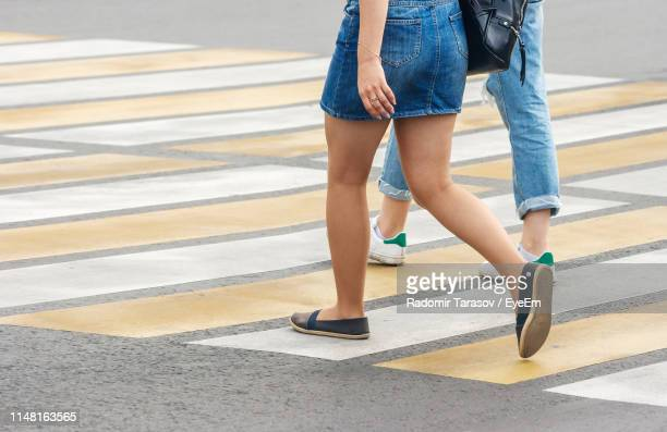 low section of women walking on road - minirok stockfoto's en -beelden