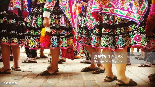 low section of women wearing colorful skirts standing on street - traditional dancing stock pictures, royalty-free photos & images