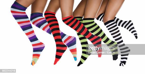 Low Section Of Women Wearing Socks Against Colored Background