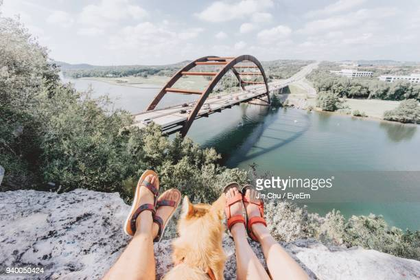 low section of women with dog on mountain against river - partie inférieure photos et images de collection