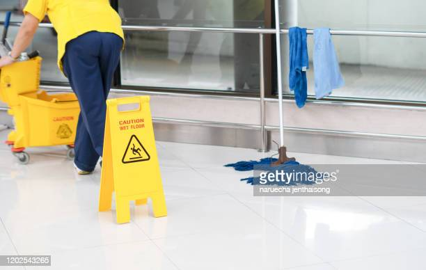 low section of worker mopping floor with wet floor caution sign on floor - daily bucket stock pictures, royalty-free photos & images