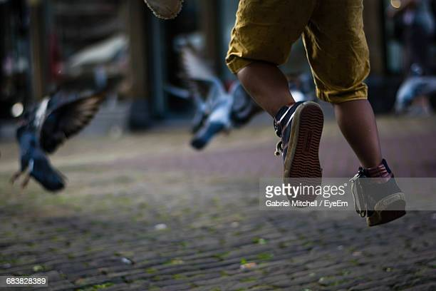Low Section Of Young Boy Jumping On The Street