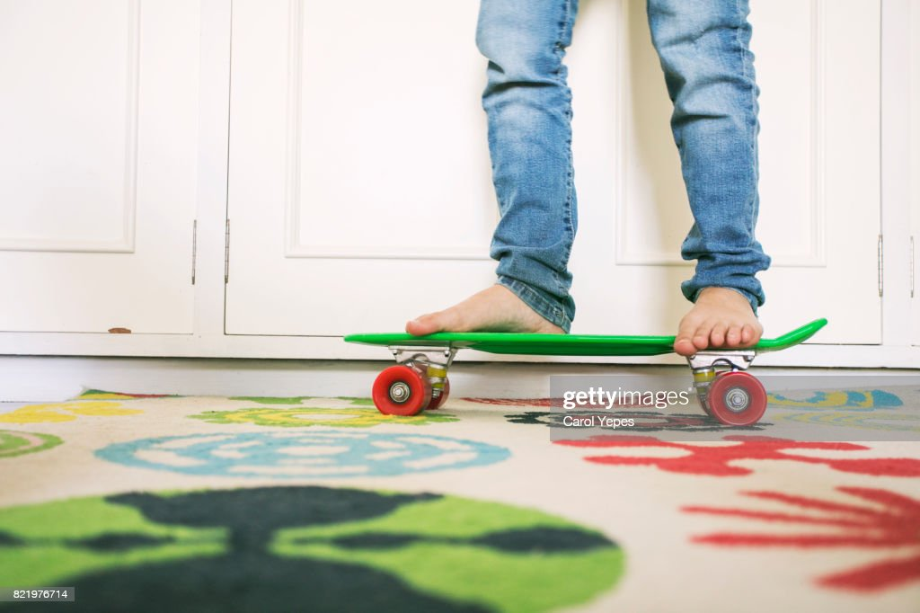 low section  of young boy skateboarding at home : Stock Photo