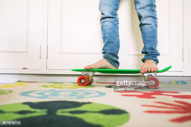low section  of young boy skateboarding at home