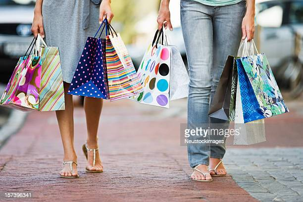 Low section of young friends holding shopping bags