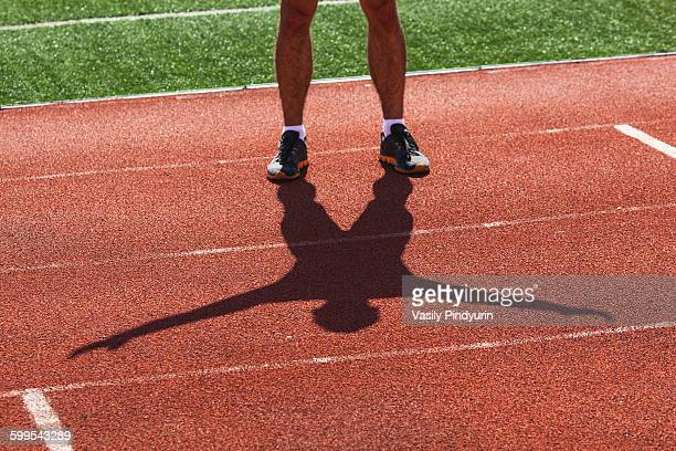 Low section of young male athlete exercising on race track