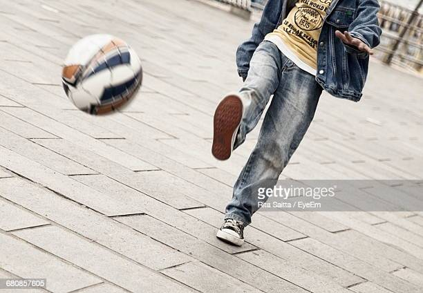 Low Section Of Young Man Playing Soccer On Paved Street