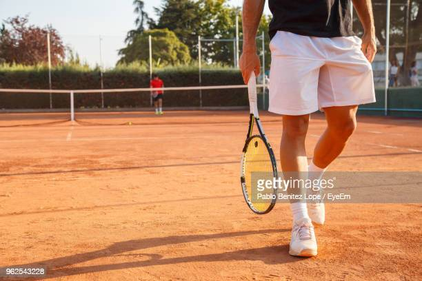 low section of young man walking with racket at tennis court - tennis stock-fotos und bilder