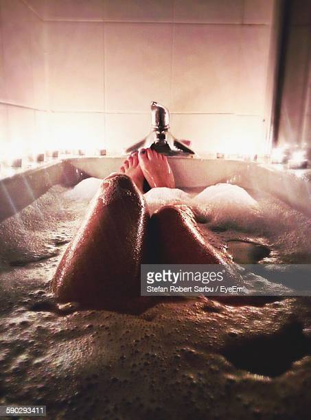 low section of young woman in bathtub - indulgence stock pictures, royalty-free photos & images