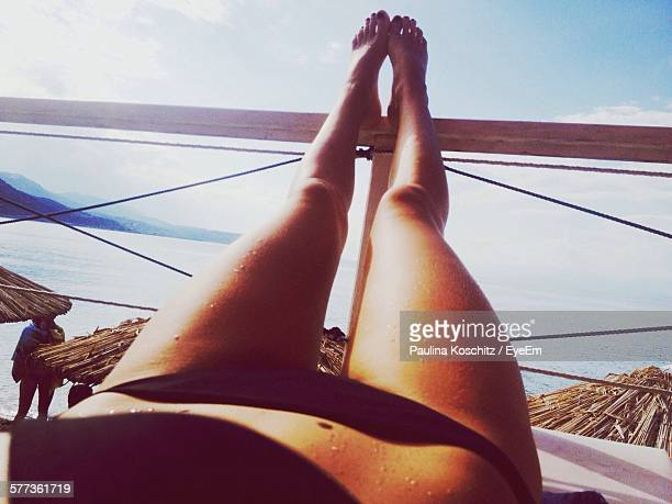 low section of young woman relaxing at beach - beautiful beach babes stock pictures, royalty-free photos & images