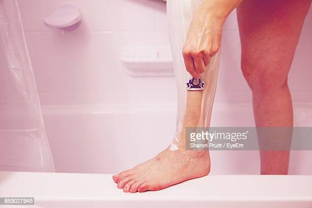 Low Section Of Young Woman Shaving Leg In Bathroom