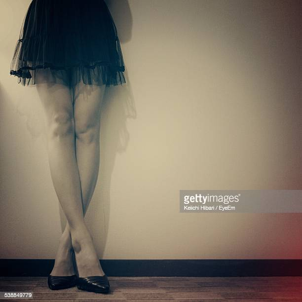 Low Section Of Young Woman Standing Legs Crossed At Knee Against Wall
