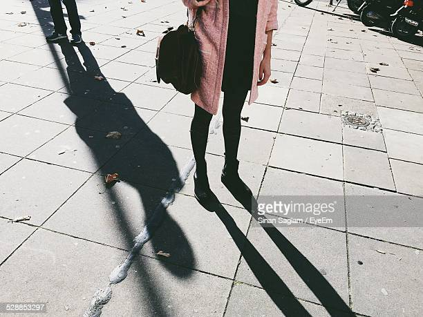 low section of young woman standing on footpath - harassment stock photos and pictures