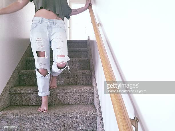 Low Section Of Young Woman Standing On Steps In Home
