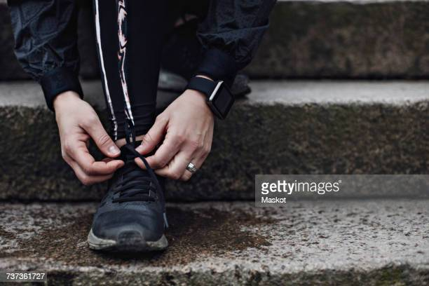 Low section of young woman tying shoelace on steps