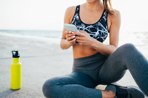 Low section of young woman using mobile phone after exercising on promenade