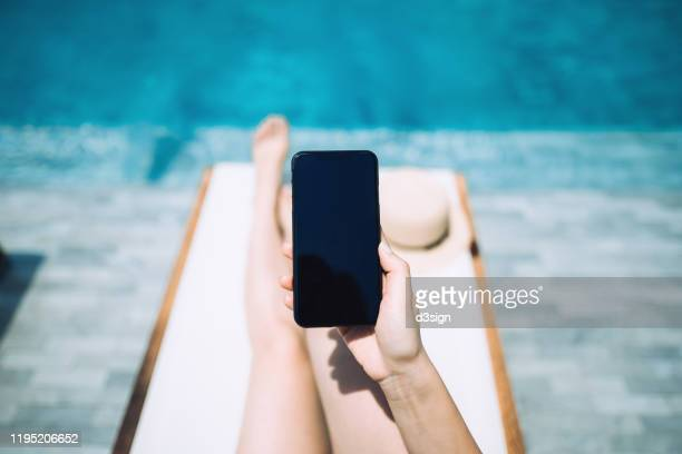 low section of young woman using smartphone while enjoying the sun on lounge chair by the pool side - 人の脚 ストックフォトと画像