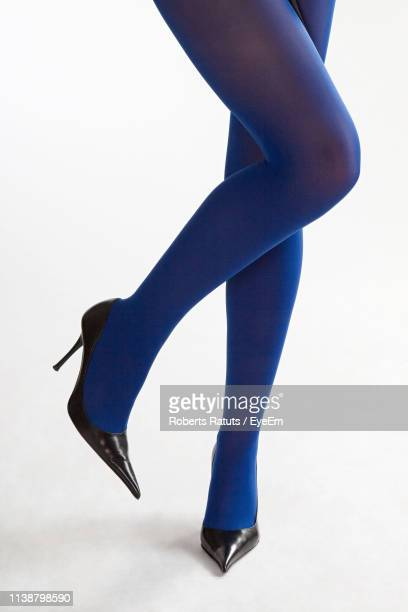 low section of young woman wearing stockings and high heels against white background - パンティストッキング ストックフォトと画像