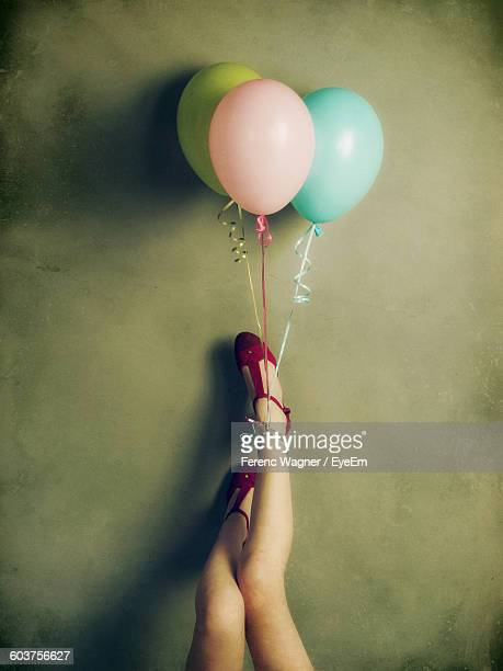 Low Section Of Young Woman With Balloons Against Wall