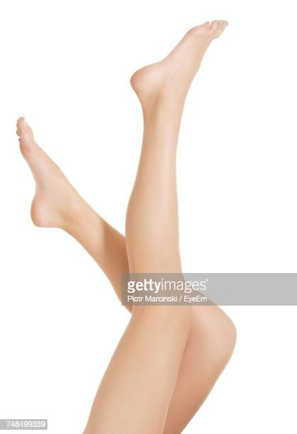 Low Section Of Young Woman With Feet Up Against White Background