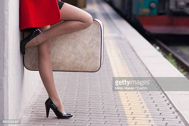 Low Section Of Young Woman With Luggage Leaning On Platform At Station