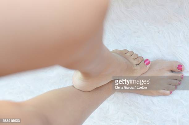 low section of young woman with pink nail polish standing on floor - beautiful female feet stock photos and pictures