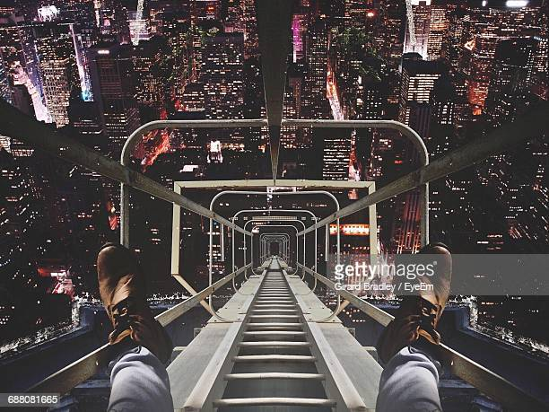 low section on man on metallic ladder over illuminated cityscape at night - unusual angle stock pictures, royalty-free photos & images
