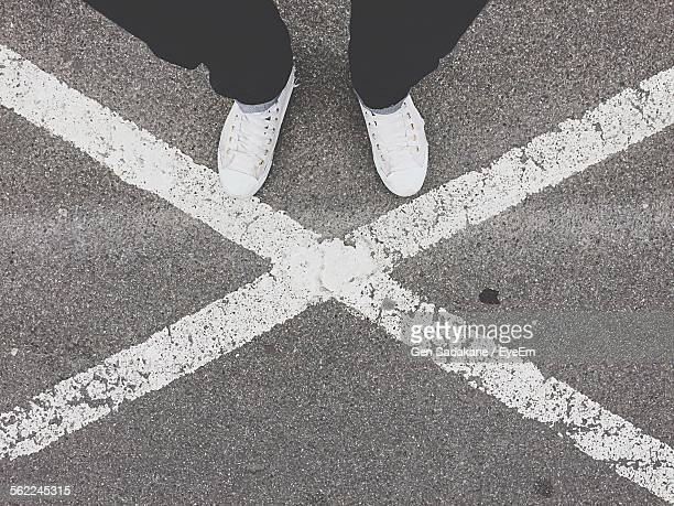 low section on man standing on road - cross shape stock pictures, royalty-free photos & images