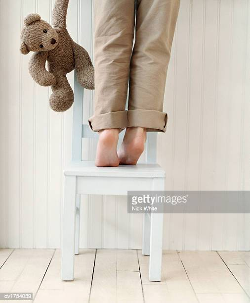 Low Section Rear View of a Child Standing Tip-Toe on a Chair by a Wall, a Teddy Bear Hanging by Their Side