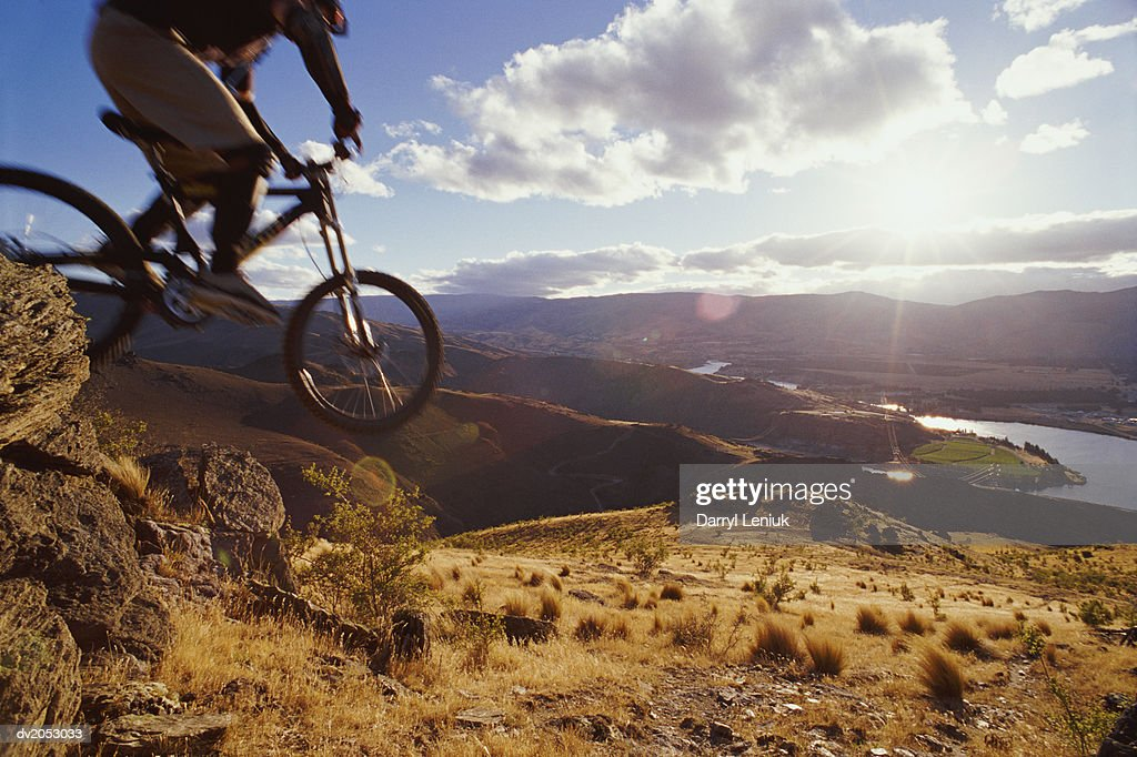 Low Section Shot of a Cyclist Riding a Mountain Bike Down a Hill, Otago, New Zealand : Stock Photo
