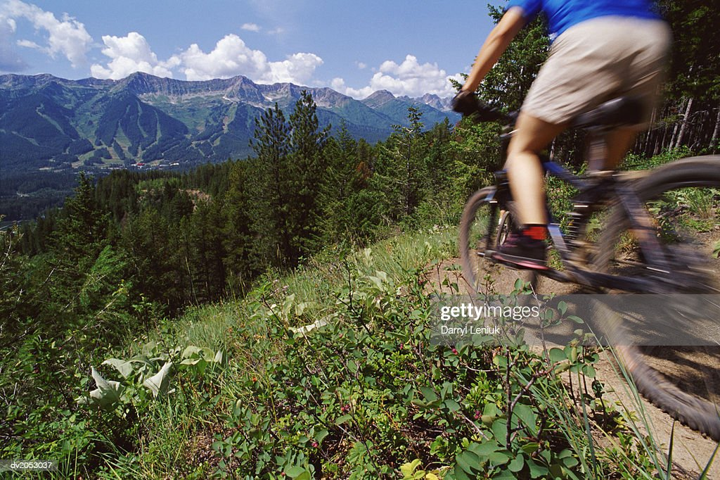 Low Section Shot of a Cyclist Riding a Mountain Bike in a Scenic Landscape : Stock Photo