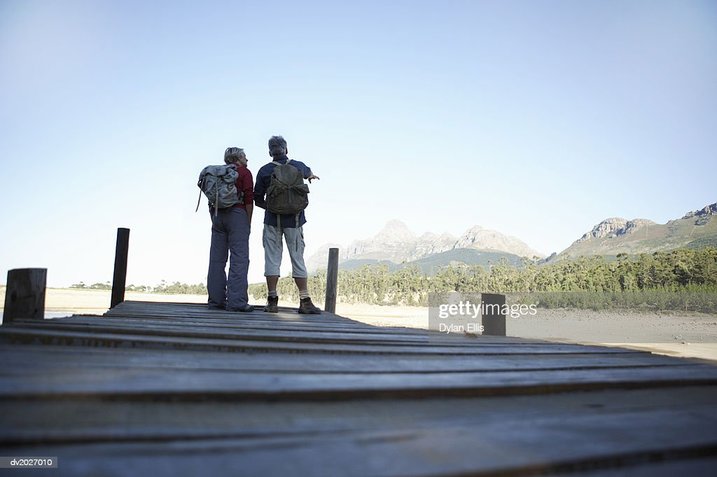 Low Section Shot of a Mature Couple Standing on a Pier, Wearing Back Packs : Stock Photo