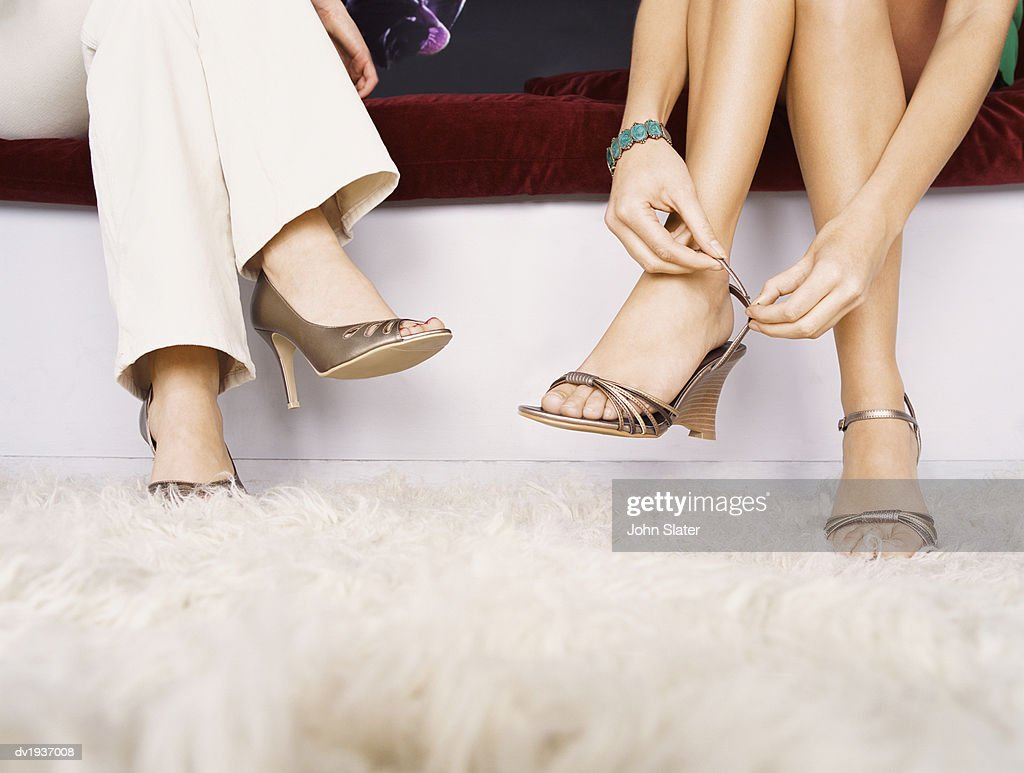 Low Section Shot of Two Women Sitting on a Sofa, One Woman Fastening Her High Heels : Stock Photo