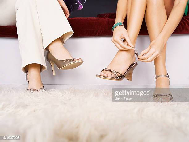 Low Section Shot of Two Women Sitting on a Sofa, One Woman Fastening Her High Heels