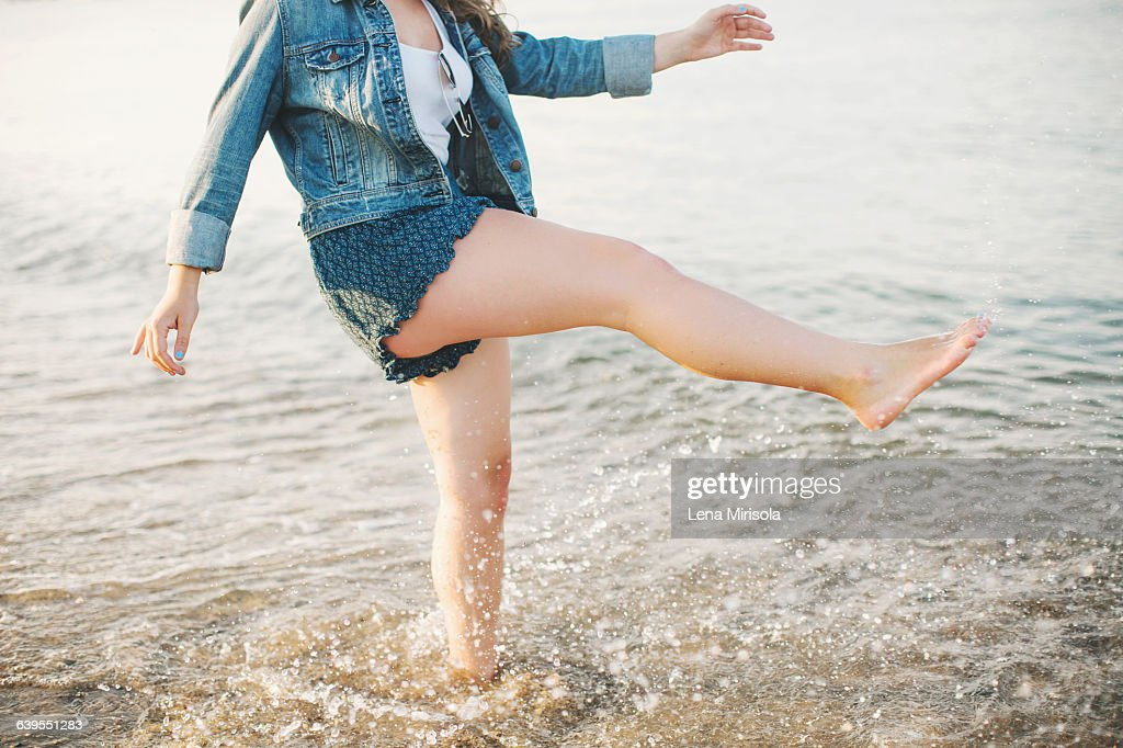 Low section side view of woman on one leg paddling in ocean : Stock Photo