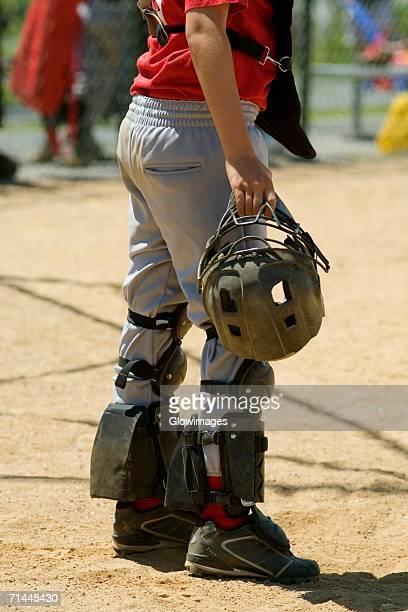low section view of a baseball catcher holding a helmet - caneleira roupa desportiva de proteção imagens e fotografias de stock