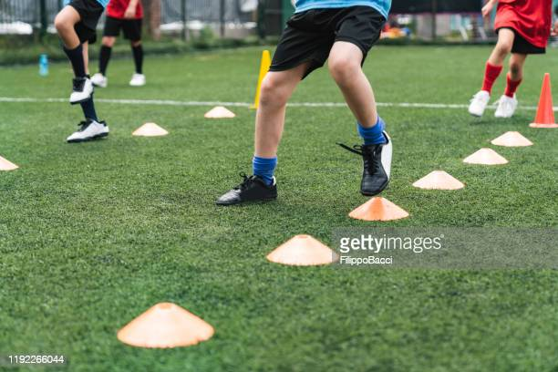 low section view of a boys soccer players practicing on field with soccer drills - studded stock pictures, royalty-free photos & images