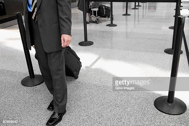 Low section view of a businessman pulling his luggage